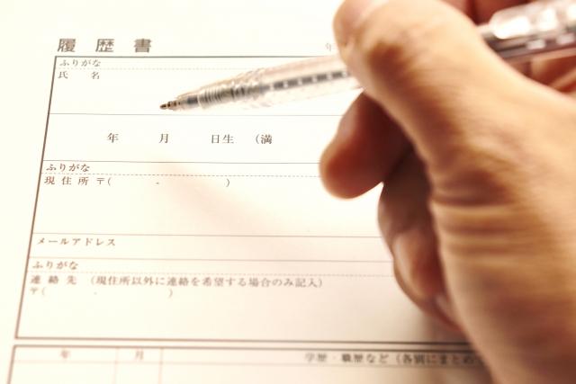 履歴書を書く男性の手